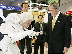 Alex Hubo, em foto tirada em feira na Ásia, saúda o presidente dos EUA, George Bush