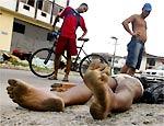 Homens observam corpo de vítima da chacina