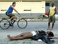 Pedestres observam o corpo de vítima da chacina no chão de uma  rua   de Nova Iguaçu