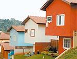 Três casas de vila pintadas com tinta à base de terra, da Primamatéria