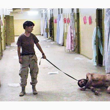 Soldado segura o que aparenta ser uma coleira de cachorro presa ao pescoço de um prisioneiro iraquiano