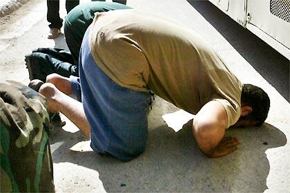 Detentos beijam o chão depois de serem soltos da prisão de Abu Ghraib, nas proximidades de Bagdá, no Iraque