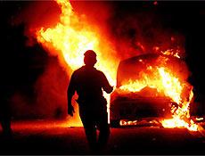 Mexicano passa por um veículo em chamas