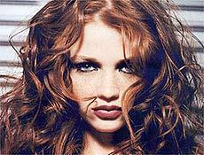 Cabelo ruivo, o rosto completamente tomado de sardas são marcas da modelo Cintia Dicker