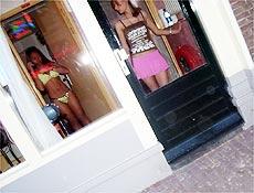"""Garotas de programa se exibem em vitrine no """"bairro da luz vermelha"""", à espera de clientes"""