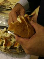 Pastor parte o pão para distribuir a fiéis