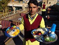 Garçom serve comida em restaurante de Isfahan