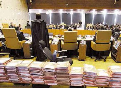 Autos do processo do mensalão, totalizando cerca de 50 mil páginas; o relator, ministro Joaquim Barbosa, de pé, durante o primeiro dia do julgamento, no plenário do Supremo