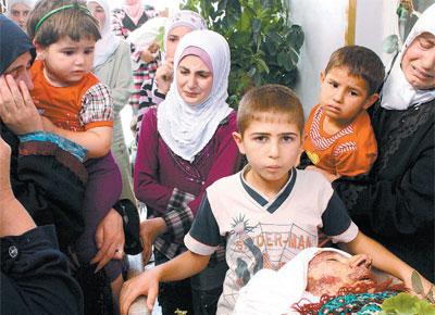 Sírios velam corpo de parente em Qusayr; ONU e EUA elevaram a pressão sobre o regime de Assad após massacre com 220 mortos