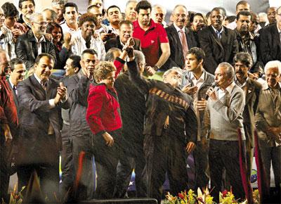 Ao lado de Michel Temer (dir.), candidato a vice, Lula ergue braço de Dilma em palanque