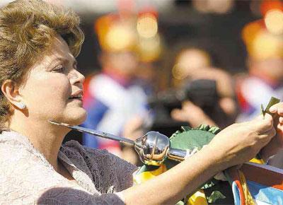<b>NÓ MILITAR:</b> Dilma Rousseff amarra condecoração em estandarte durante a comemoração do Dia do Exército