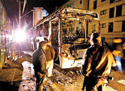 Policiais observam ônibus que foi incendiado por dois criminosos em Diadema, na Grande São Paulo, na madrugada