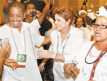 A petista Dilma Rousseff a noite, participa ao lado de mãe de santo de encontro do movimento negro organizado pelo PT